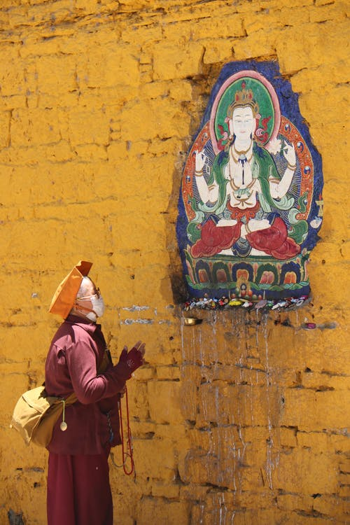 Person Praying in Front of a Buddha Painting