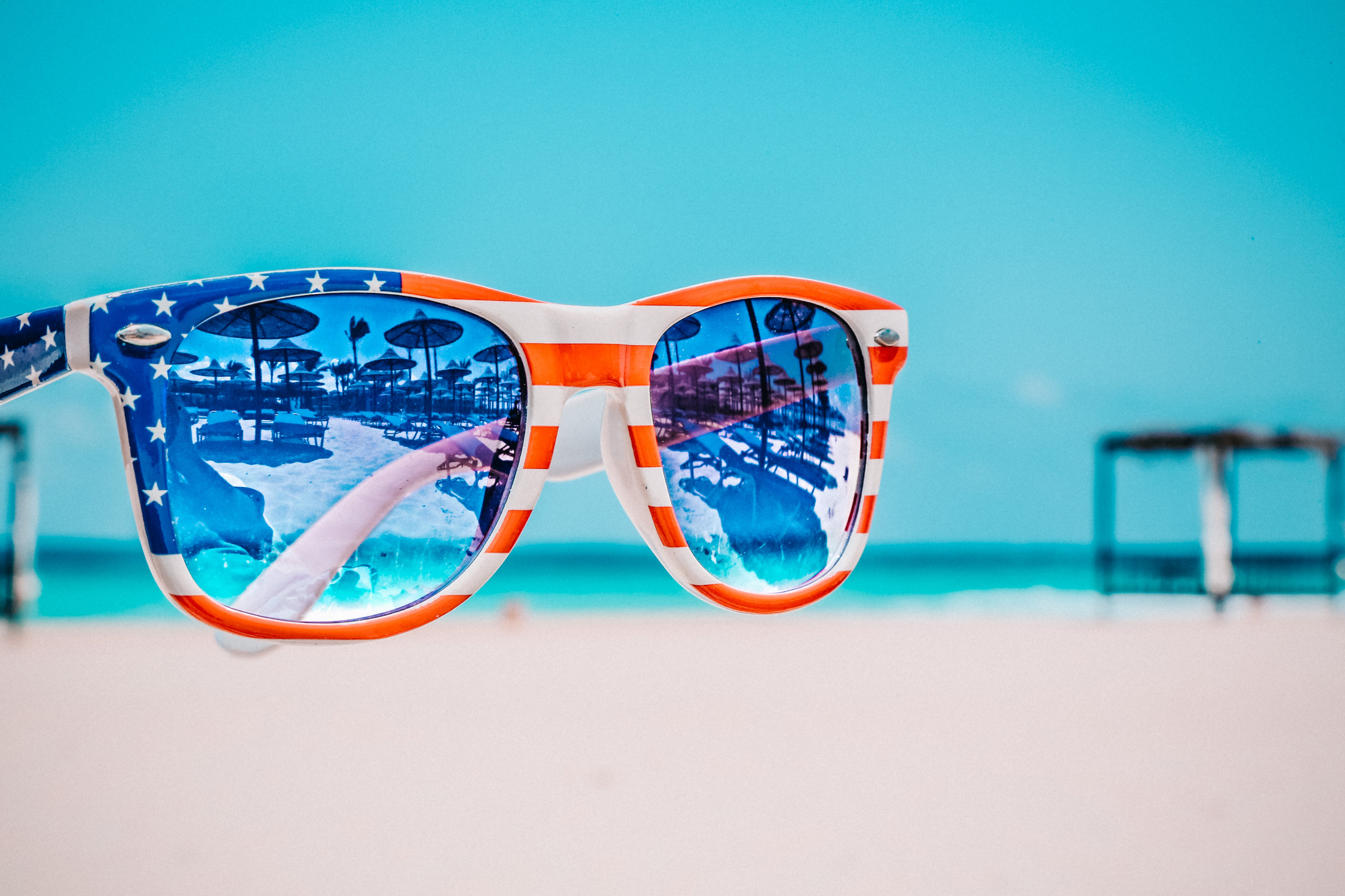Focus Photography of American Flag-accent Wayfarer-styled Sunglasses With Sea Background