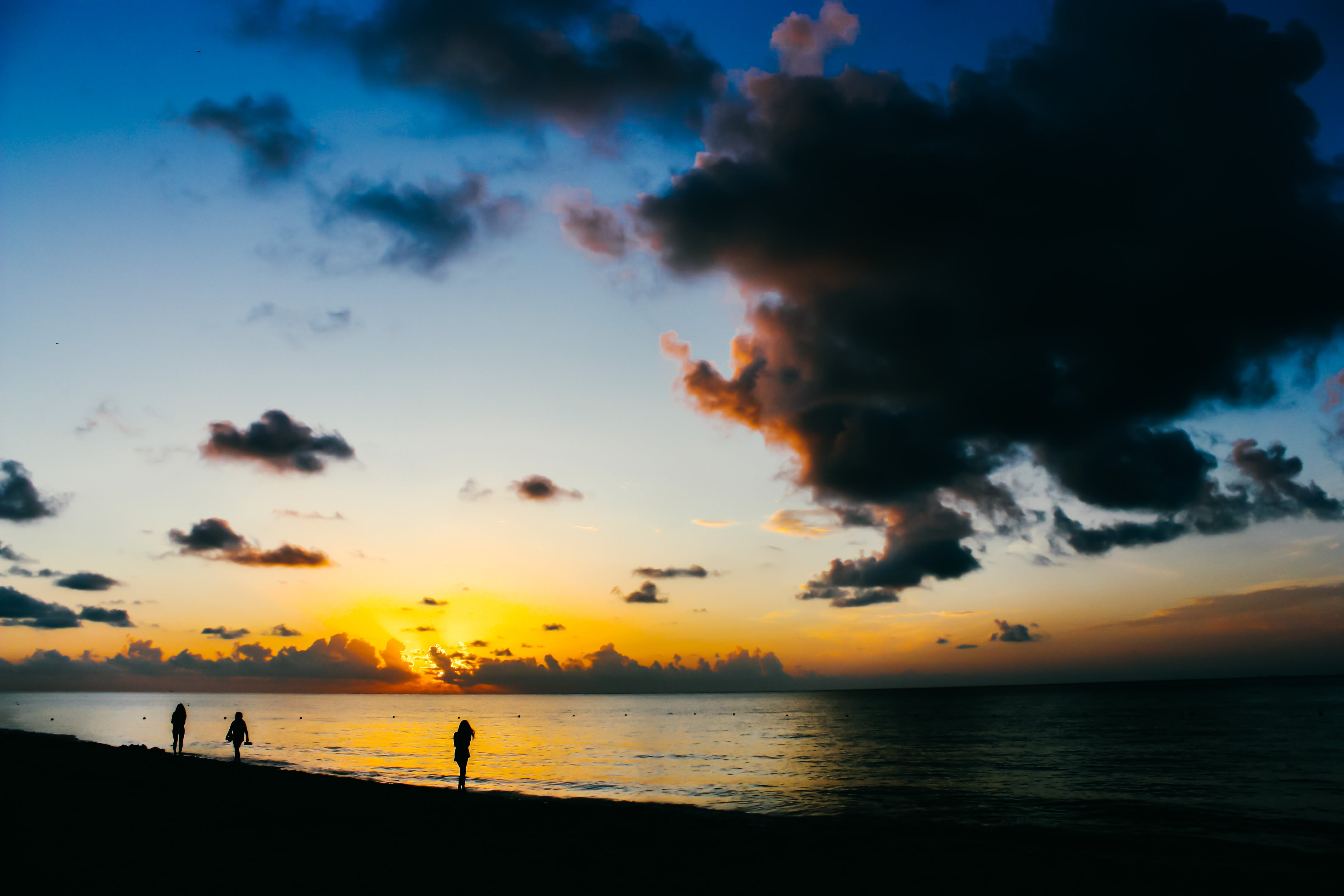 People Standing on Seashore during Sunset