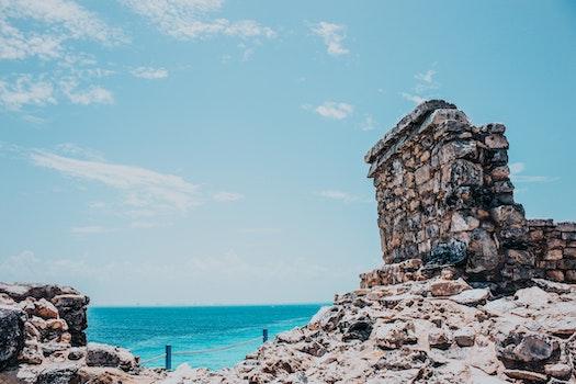 Rocky Terrain Near Sea Under Blue Skies