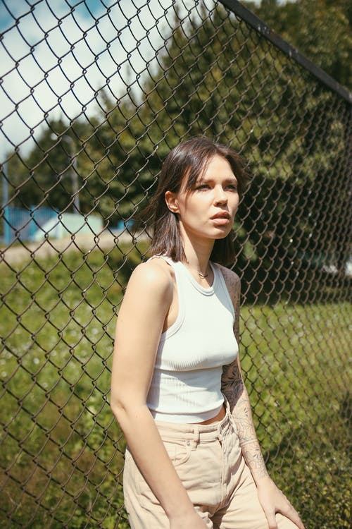 ショートヘア, フェンス, ホワイトタンクトップの無料の写真素材