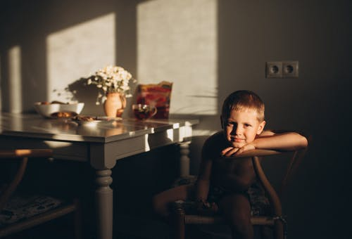 Shirtless Boy Sitting on a Chair while Looking at Camera