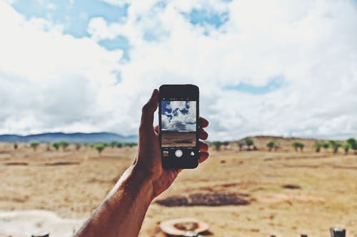 Person Holding Smartphone Showing Cloudy Sky