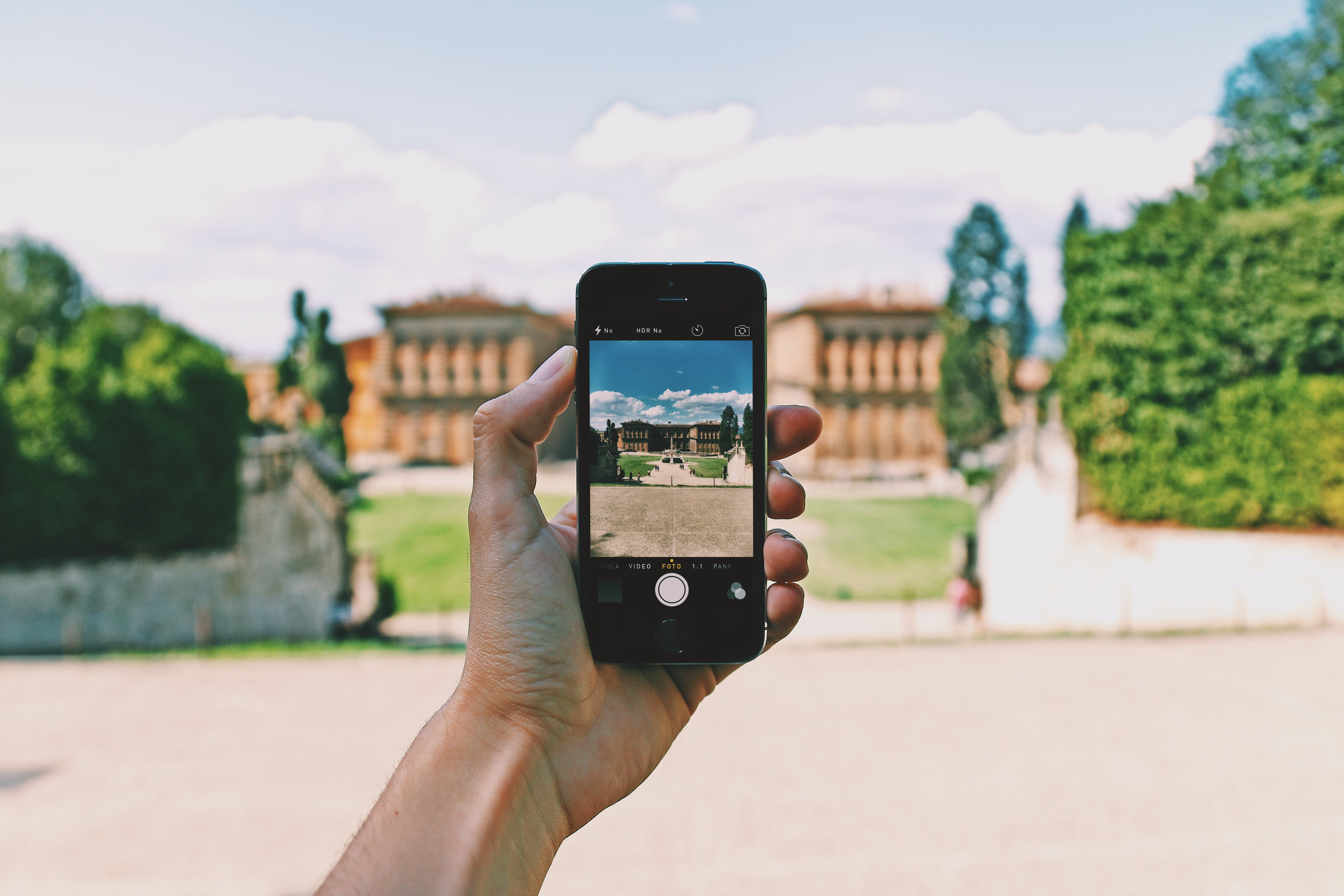 Person Using Space Gray Iphone 5s Taking a Picture of Landmark during Day