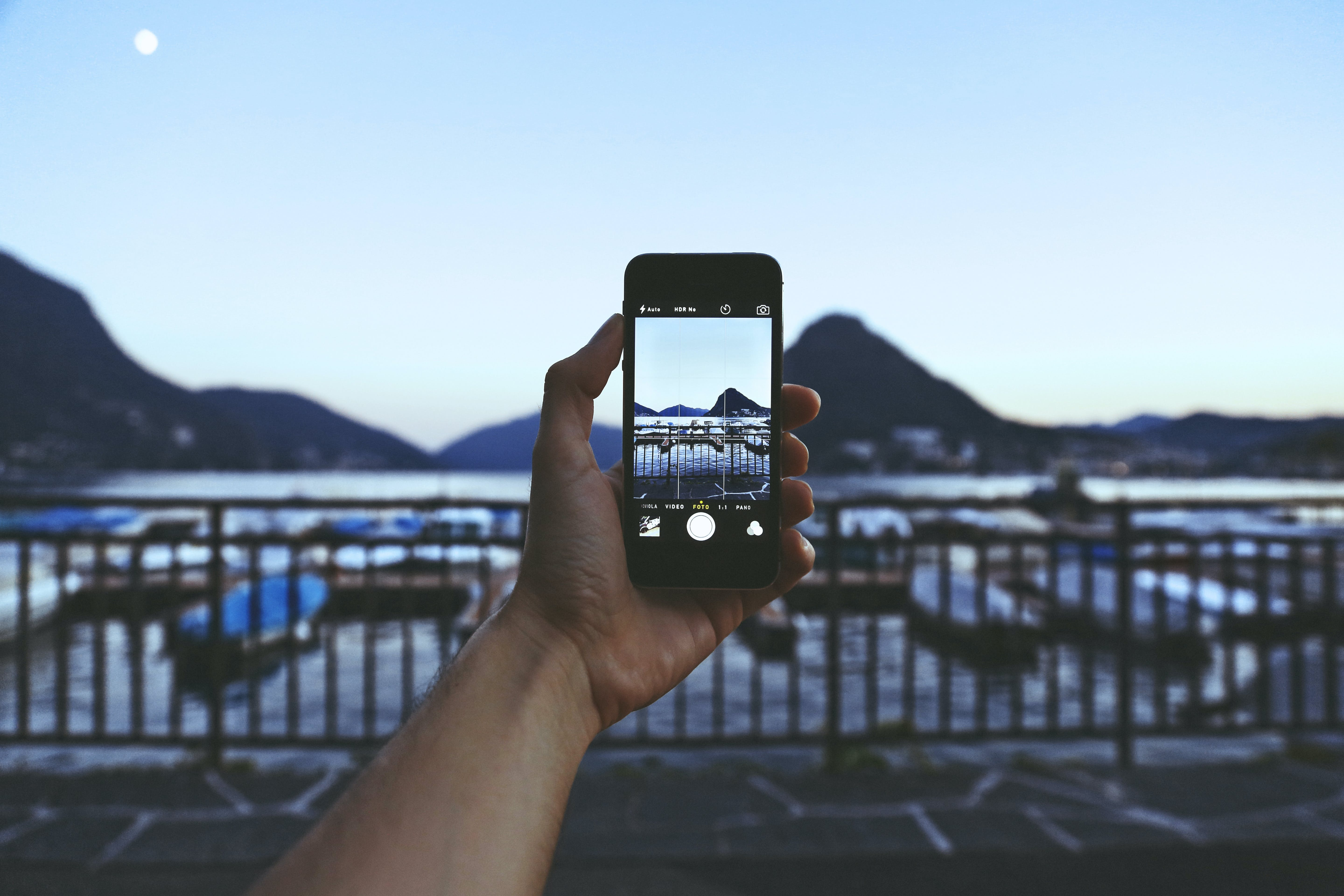 Person Holding Iphone Taking Picture of Mountain Near Body of Water