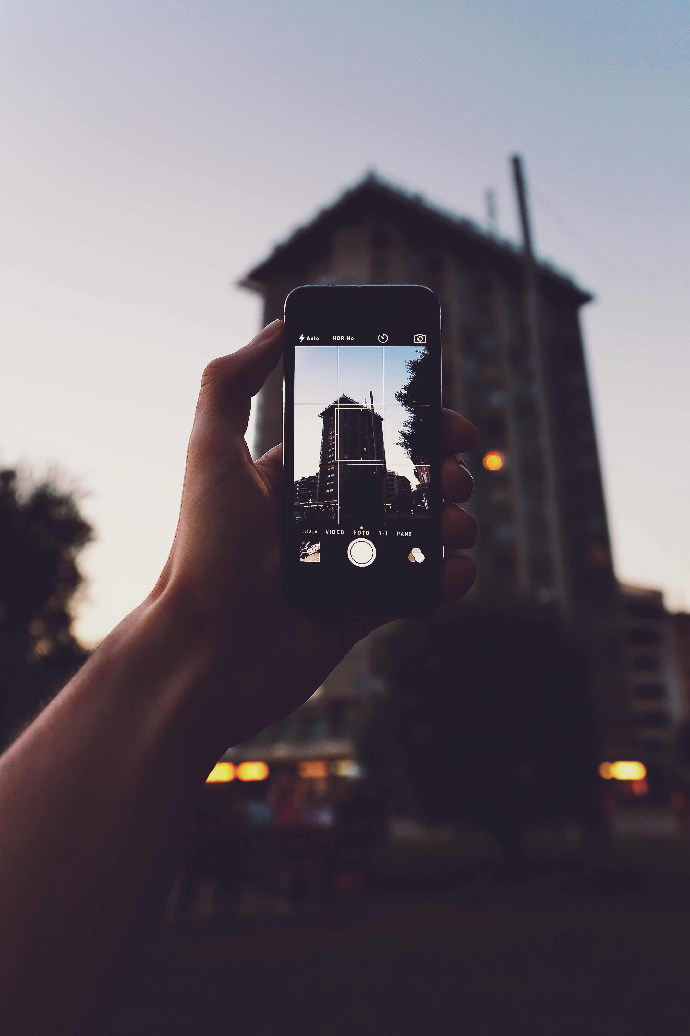 Person Holding Iphone Taking a Photo of Building
