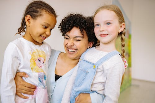 Woman Hugging Two Kids With A Big Smile On Her Face