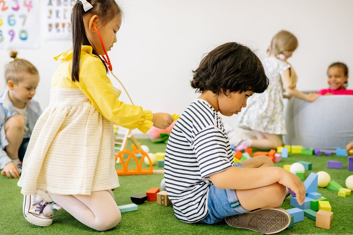 Girl in Yellow Dress Playing Doctor With A Boy In Striped Shirt