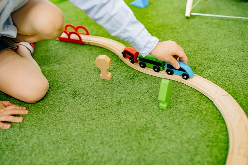Child Playing With Wooden Toy Cars