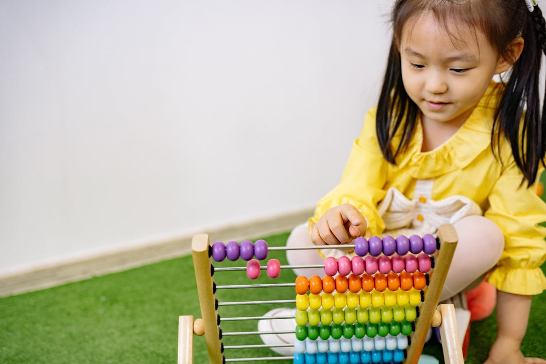 Girl in Yellow Dress Playing With Abacus