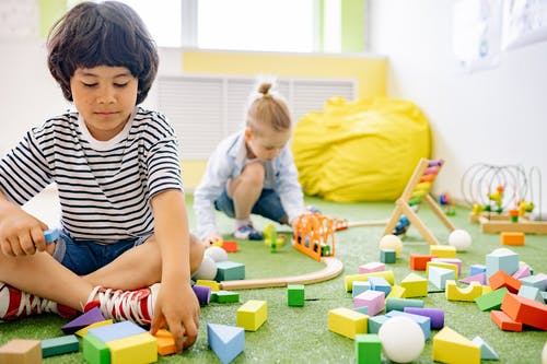 Two Boys Playing With Wooden Blocks in a Room