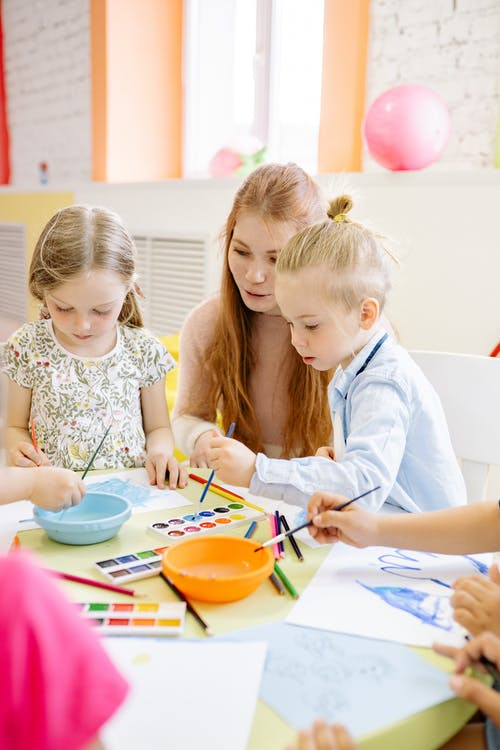 Kids Painting With Water Color On White Paper