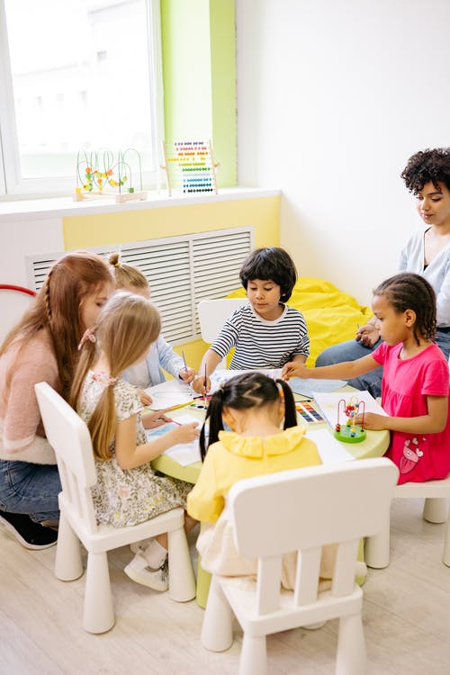Group of Children Sitting Around A Table And Doing Art
