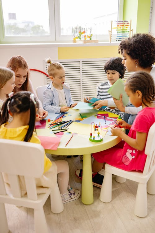 Children Sitting on Chairs in Front of Table With Art Materials