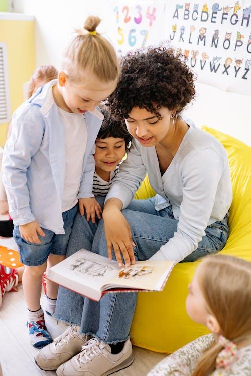 School Teacher Showing A Book To The Children