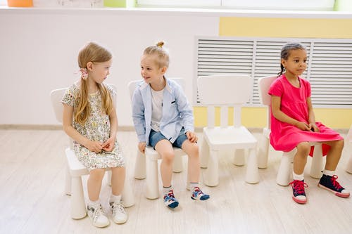 Girl and Boy Talking While Sitting Inside The Classroom