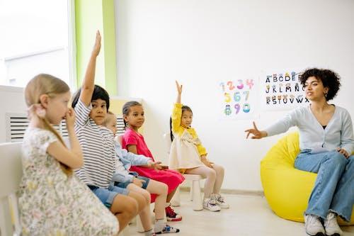 Teacher Giving Lesson and Children Raising Their Hands