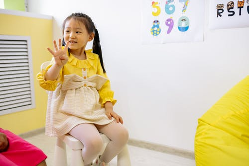 Girl in Yellow and White Dress Learning To Count With Her Fingers