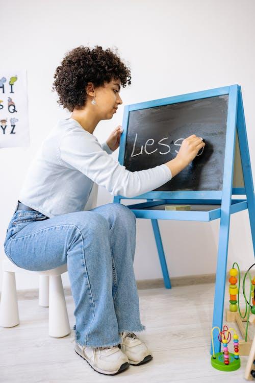 Woman in White Dress Shirt and Blue Denim Jeans Writing On Blackboard