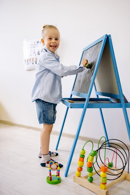 Child in Blue Long Sleeve Shirt and Blue Denim Shorts Learning To Draw On Blackboard