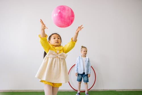 Girl in Yellow Dress Playing With Pink Balloon