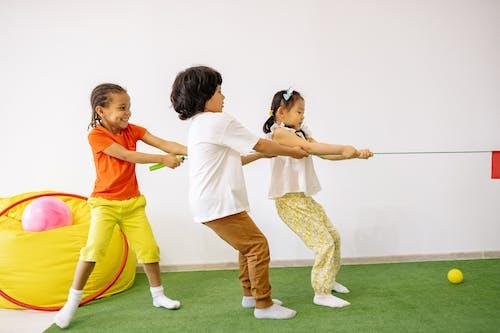 Children Playing Tug Of War On Green Carpet