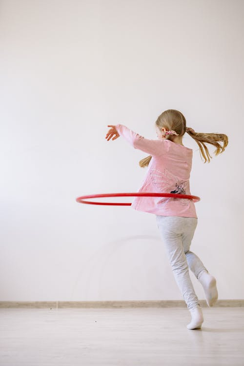 Girl in Pink Shirt and White Pants Jumping