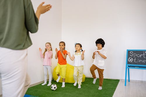Children Playing With Their Teacher on Green Carpet