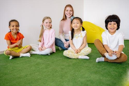 Happy Children And Teacher Sitting on Green Grass Carpet