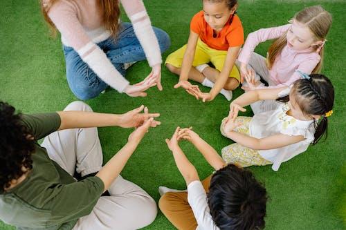 Preschool Children Doing Hand Exercise With Teachers
