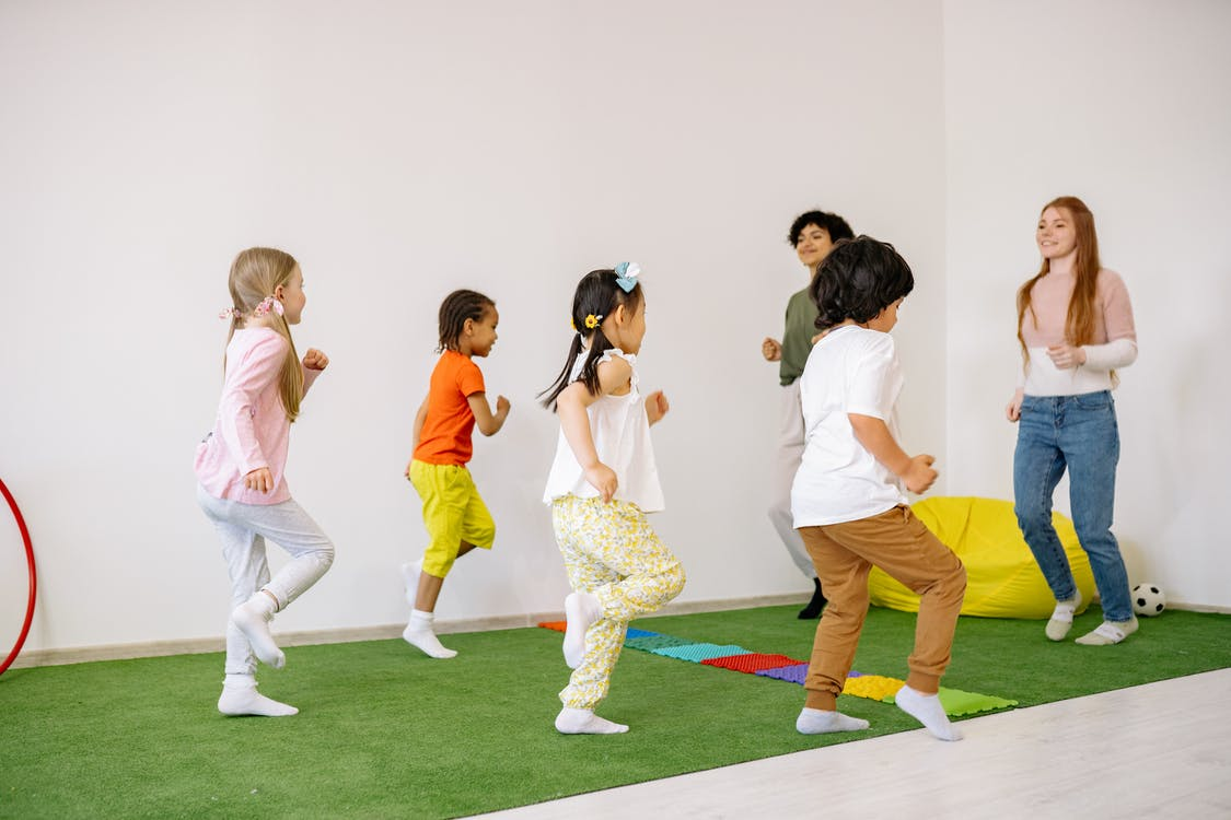 Preschoolers Doing Running Exercise With Their Teachers