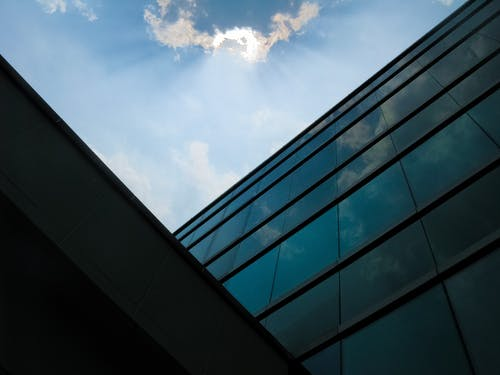 Blue and White Cloudy Sky over Glass Walled Building