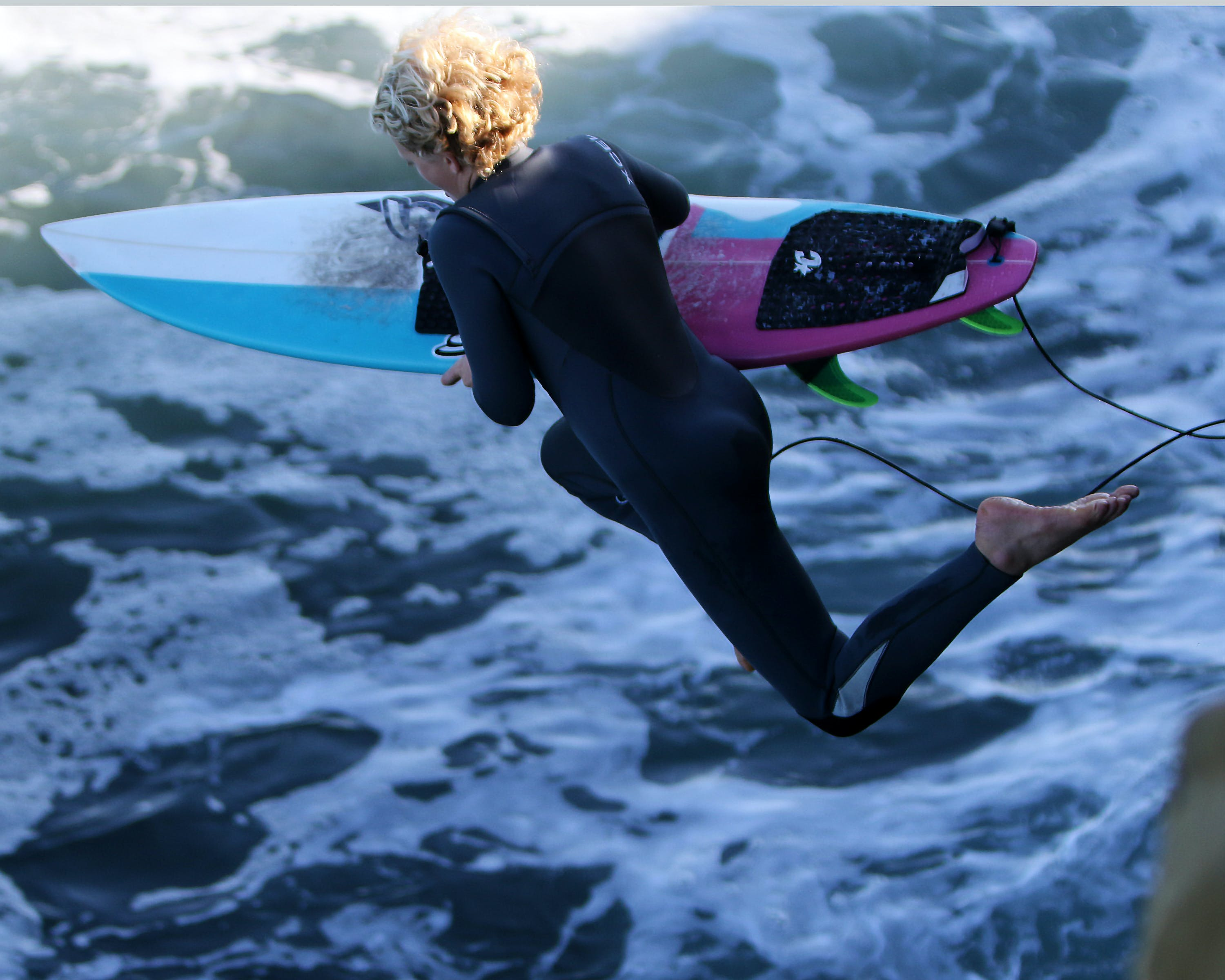 Woman With Surfboard Jumping to Body of Water