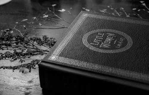 Grayscale Photo of a Book on a Wooden Surface