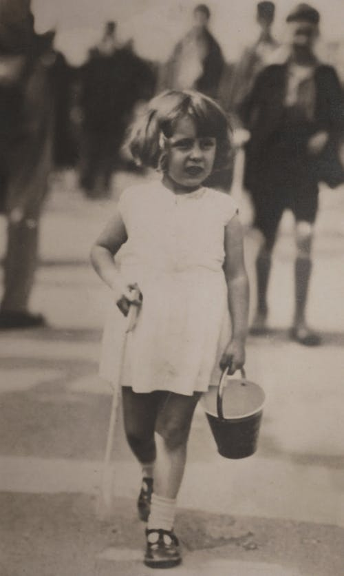 Lost Girl in White Sleeveless Dress Holding Bucket