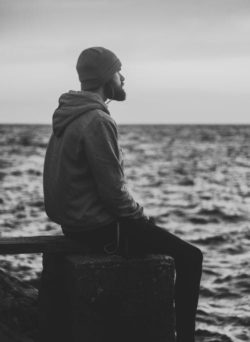 Grayscale Photo of Man in Hoodie and Kit Cap Sitting Near Bodies of Water