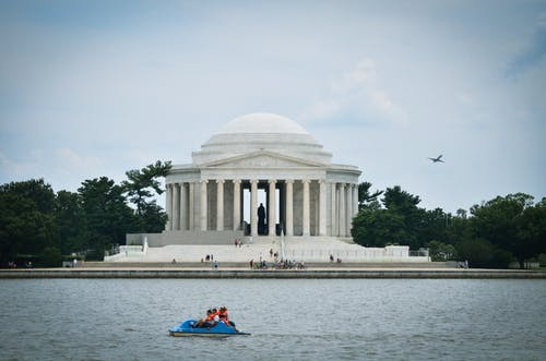 People Riding on Red Kayak on Body of Water Near White Concrete Building