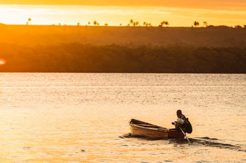 Man and Woman Riding on Boat during Sunset