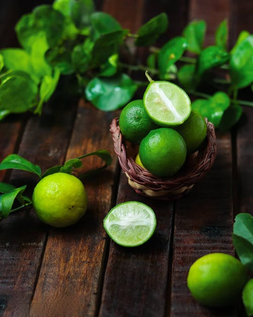 Close-Up Shot of Limes on a Wooden Surface