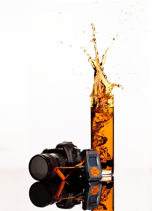 Black Canon Dslr Camera Behind Clear Highball Glass