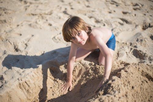 Woman in Blue Bikini Sitting on Brown Sand