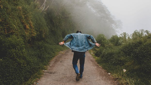 Person Wearing Blue Denim Jacket While Walking on Foggy Road - Boohoo