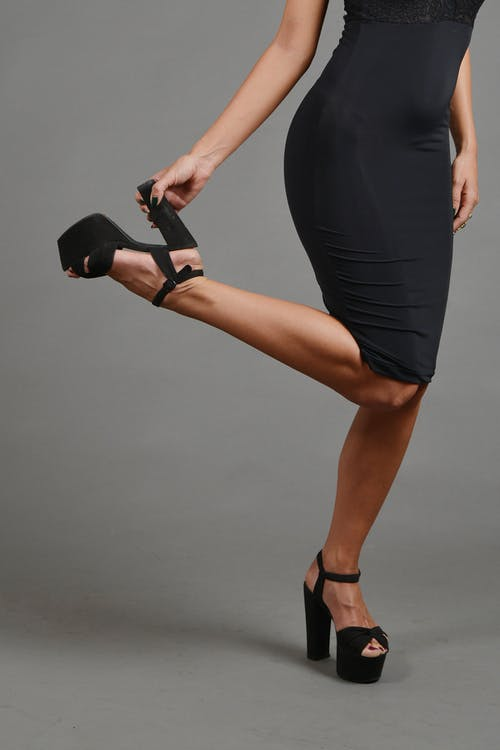 A Woman in Black Dress Holding Her Stiletto Heels