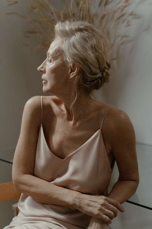 An Elderly Woman in Beige Dress Looking to Her Right