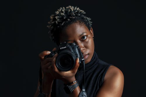 A Woman with Short Hair Holding a Digital Camera on Black Background