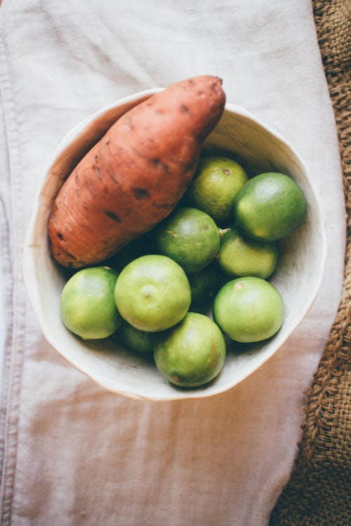Green and Brown Round Fruits on White Ceramic Bowl