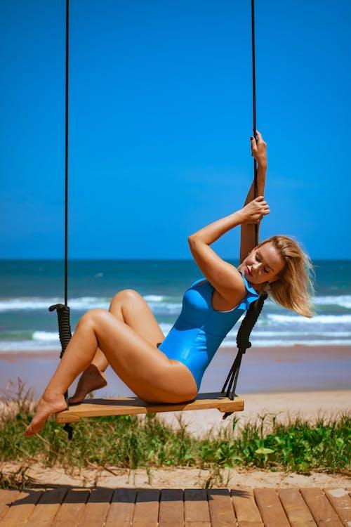 Woman in Blue Swimsuit Sitting on Swing
