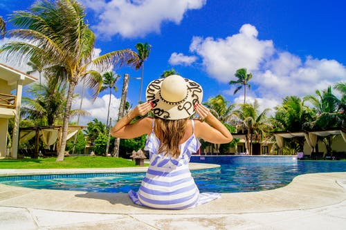 Woman in White and Blue Stripe Tank Top and White Hat Standing on Swimming Pool during