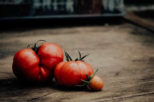Close-Up Shot of Fresh Tomatoes on a Wooden Table