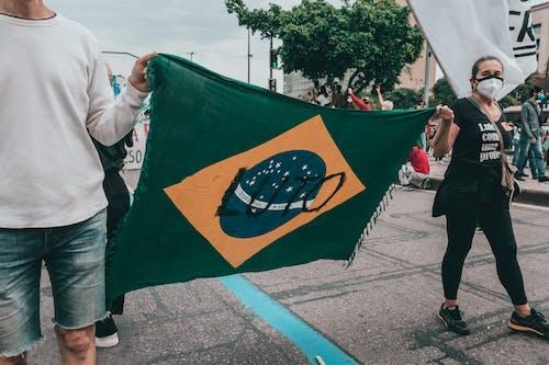 Man in White Dress Shirt Holding Green Flag